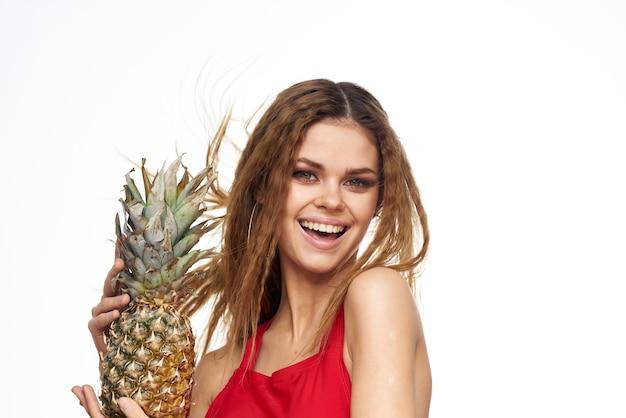 Frau mit ananas in den händen welliges haar rotes t-shirt früchte sommerferien lichtwand.