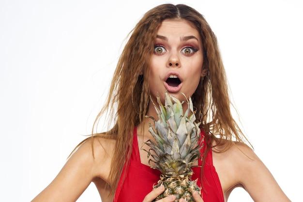 Frau mit ananas in den händen welliges haar rotes t-shirt früchte sommerferienlicht.