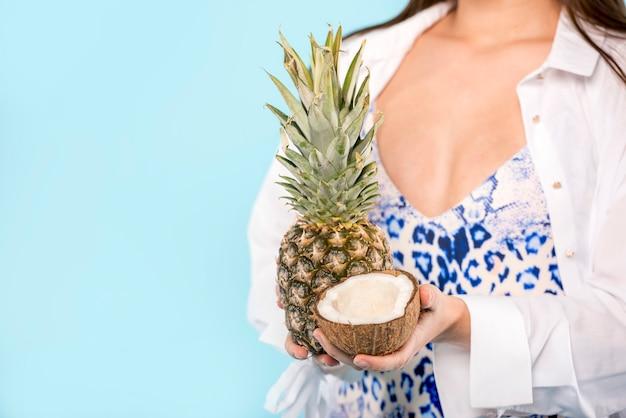 Frau mit ananas und kokosnuss