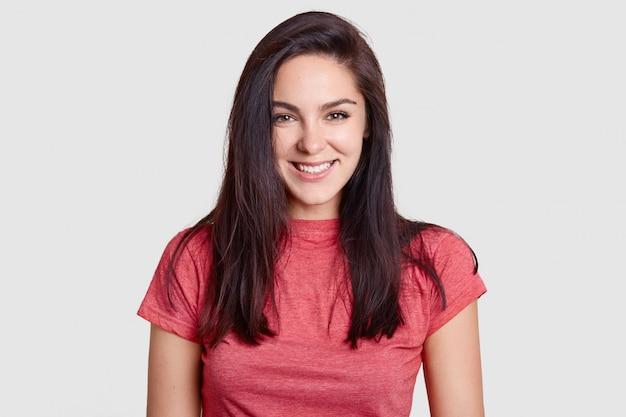 Frau mit angenehmem lächeln, dunklem haar, gekleidet in lässigem rosa t-shirt, hat weiße perfekte zähne, freut sich über komplimente