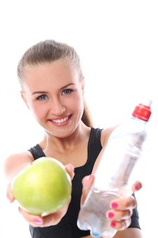 Frau mit apfel und flasche frischem wasser