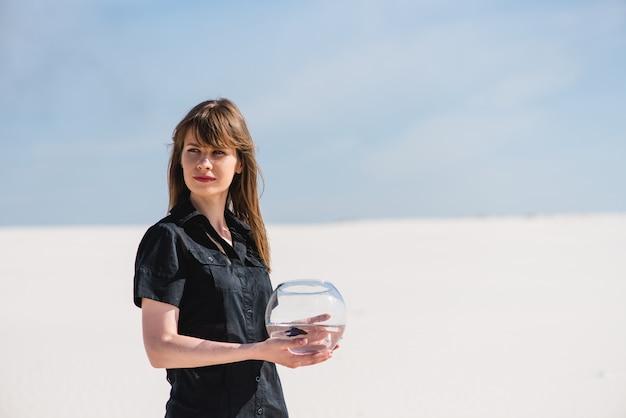 Frau mit aquarienfischen in der wüste