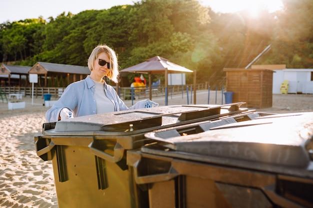 Frau mit arbeitshandschuhen mit grünen müllcontainern, die morgens den strand aufräumen