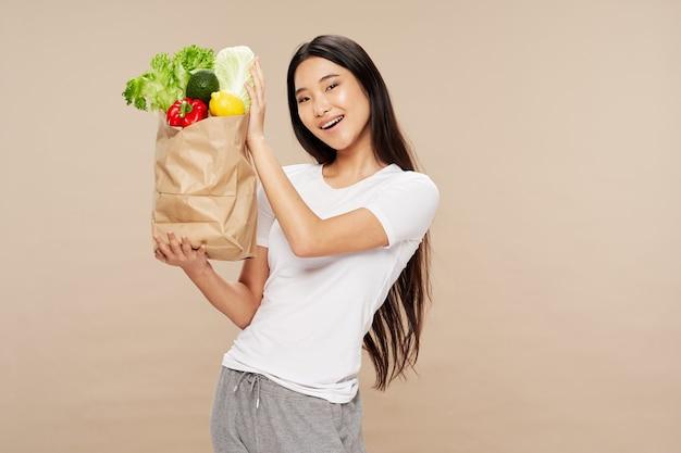 Frau mit asiatischem aussehen in einem paket mit gesundem essen des gemüses