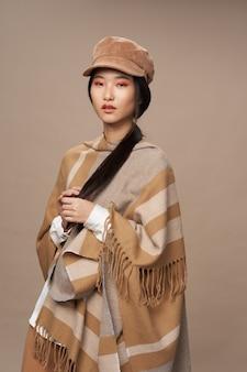 Frau mit asiatischem aussehen in traditioneller kleidung mode beige hintergrund