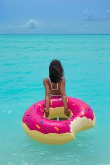 Frau mit aufblasbarem donut im meer