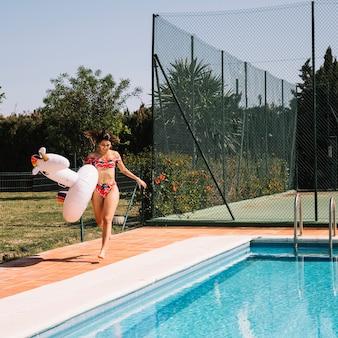 Frau mit aufblasbarem Einhorn nahe bei Pool