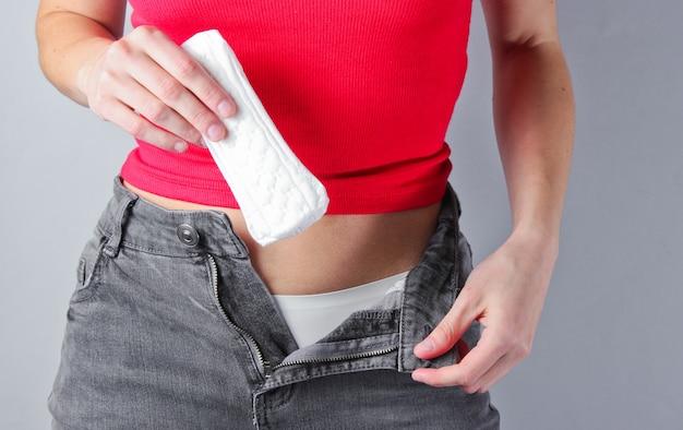 Frau mit aufgeknöpfter jeans hält polster in ihren händen.