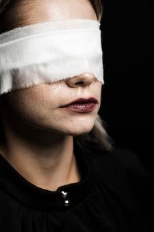 Frau mit augenbinde auf schwarzem hintergrund
