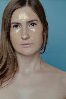 Frau mit augenflecken. hautpflege, frauenschönheit, hygiene und persönliches pflegekonzept. unter den augenklappen auftragen, augenmaske gegen augenringe und schwellungen.