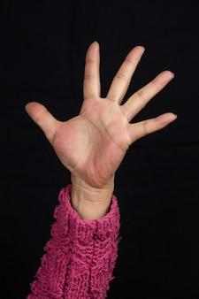 Frau mit ausgestrecktem arm in einem rosa pullover