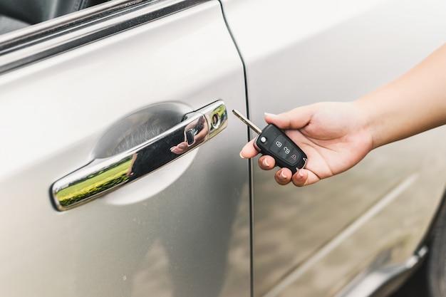 Frau mit autoschlüssel in der nähe der tür