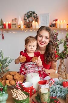 Frau mit baby in der küche für weihnachten dekoriert. neujahrsfotosession der familie.