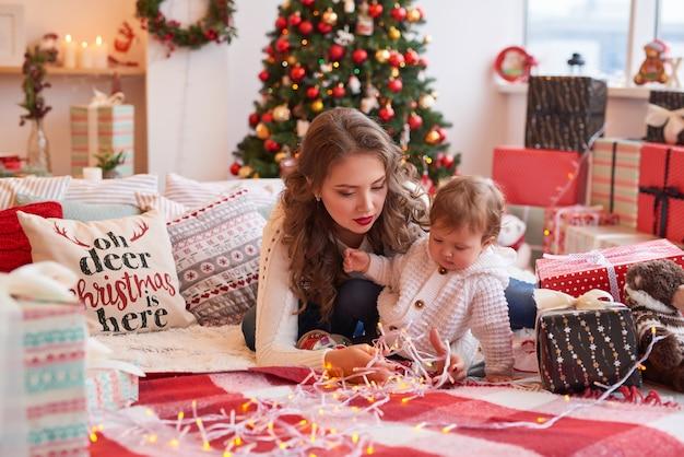 Frau mit baby in der küche für weihnachten dekoriert.