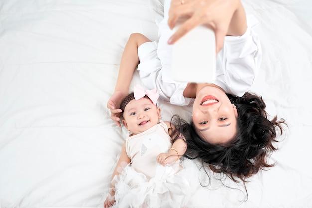 Frau mit baby macht ein selfie auf holzboden liegend