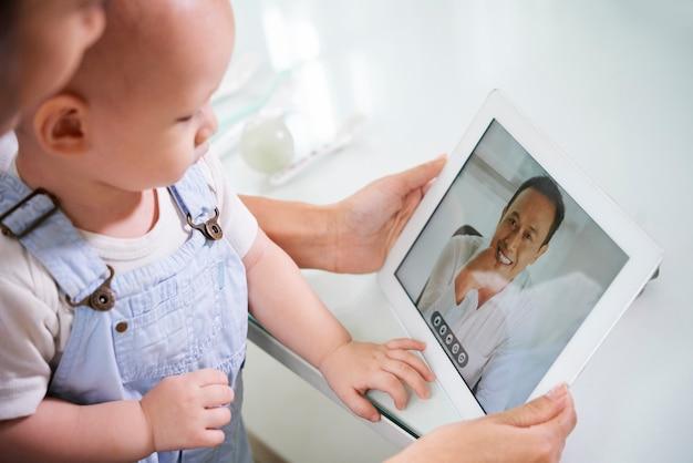 Frau mit baby video anruf ehemann