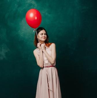Frau mit ballon in ihren händen in einem kleid,