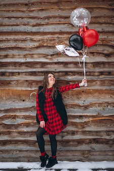 Frau mit ballonen an ihrem geburtstag draußen