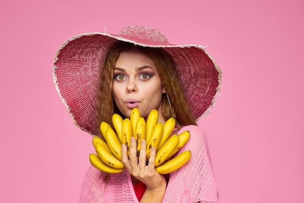 Frau mit bananen in den händen im hut exotische früchte lebensstil rosa wand.