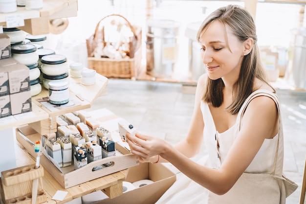 Frau mit baumwollbeutel kauft körperpflegeartikel in zero waste shop