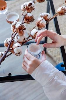 Frau mit baumwollcreme im weißen hemd zu hause.