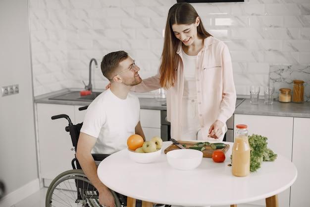 Frau mit behindertem mann im rollstuhl, der zu hause zusammen frühstückt.