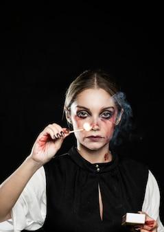Frau mit beleuchtetem match auf schwarzem hintergrund