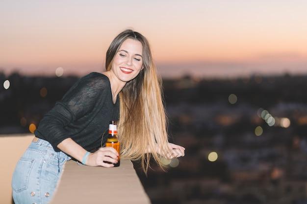 Frau mit bier auf dem dach