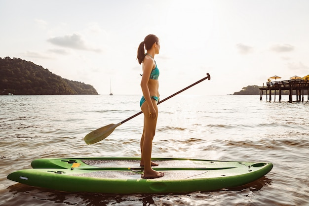 Frau mit bikini auf paddle board