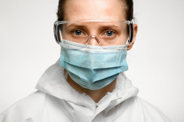 Frau mit blauen augen in der medizinischen maske und in der schutzbrille zum schutz gegen influenza.