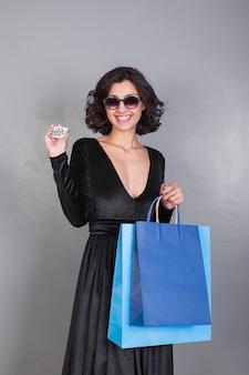Frau mit blauen einkaufstaschen und kreditkarte