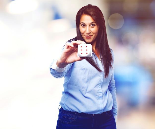 Frau mit blauen hemd, das ein würfel hält