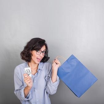 Frau mit blauer einkaufstasche und kreditkarte