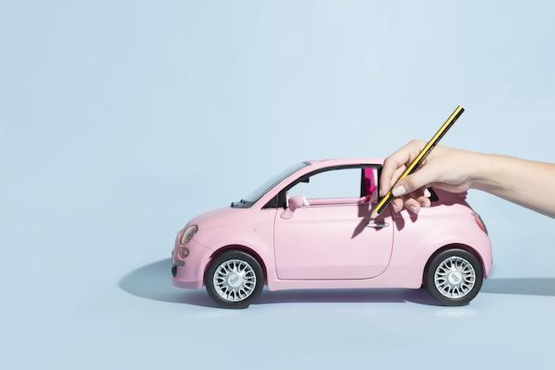 Frau mit bleistift, als würde sie ein neues auto zeichnen