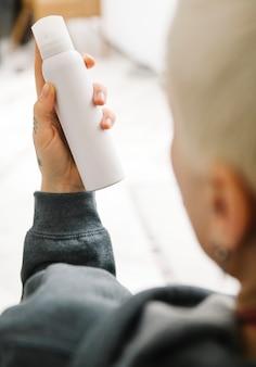 Frau mit blonden haaren, die eine weiße sprühflasche hält
