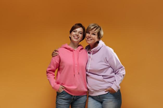 Frau mit blonden haaren in lila sweatshirt und jeans lächelnd und umarmend mit jungem mädchen mit brünetter frisur und rosa kapuzenpulli.