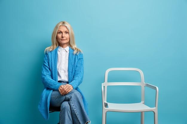 Frau mit blonden haaren trägt lässige jumper-jeans sieht selbstbewusst aus und posiert allein in der nähe eines leeren stuhls isoliert auf blau