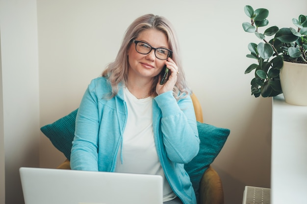 Frau mit blonden haaren und brillen, die am telefon sprechen und fern am laptop arbeiten