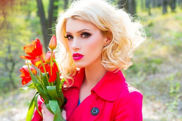 Frau mit blühenden frühlingsblumen schönes mädchen im roten kleid mit blumentulpen in den händen auf einem spr...
