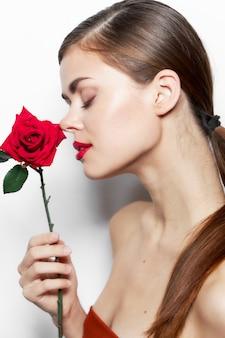 Frau mit blume schnüffelnde rote lippen geschlossen augen helle make-up nahaufnahme