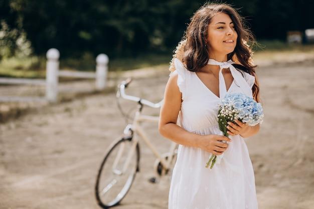 Frau mit blumen, die fahrrad am strand reiten