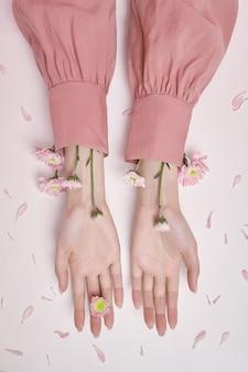 Frau mit blumen in der hand und in den ärmeln. kosmetik und handpflege. handfeuchtigkeit und anti-falten- und anti-aging-behandlung