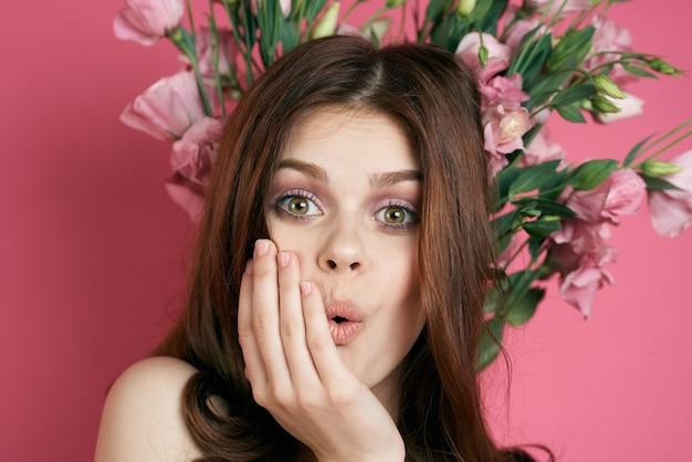 Frau mit blumen über kopf kranz emotionen spaß rosa hintergrund porträt nahaufnahme