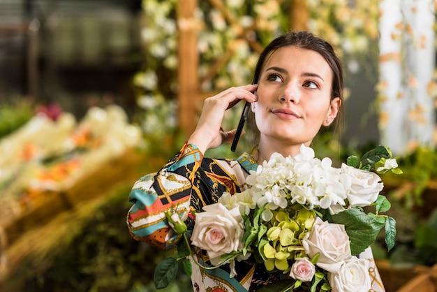 Frau mit blumenblumenstrauß telefonisch sprechend