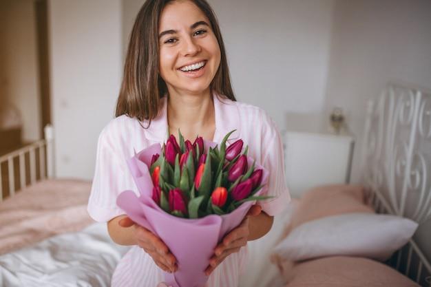 Frau mit blumenstrauß von blumen im schlafzimmer
