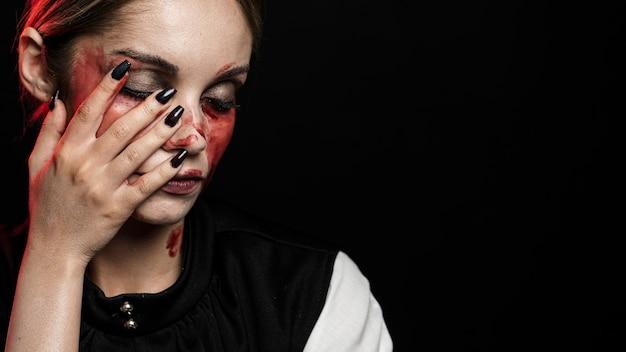 Frau mit blutigem make-up auf gesicht