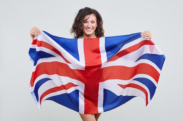 Frau mit braunen haaren, die mit der britischen flagge im studio auf einem weißen hintergrund aufwirft