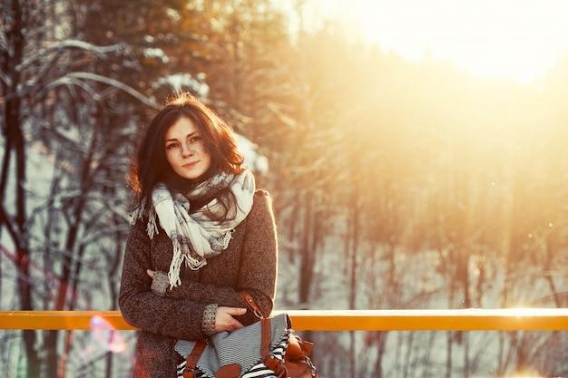 Frau mit braunen mantel verbringen den tag im schnee