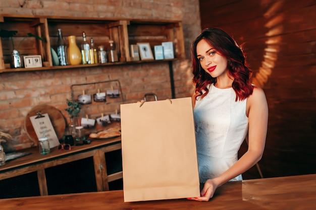 Frau mit brauner klarer papierbasteltasche auf der küche