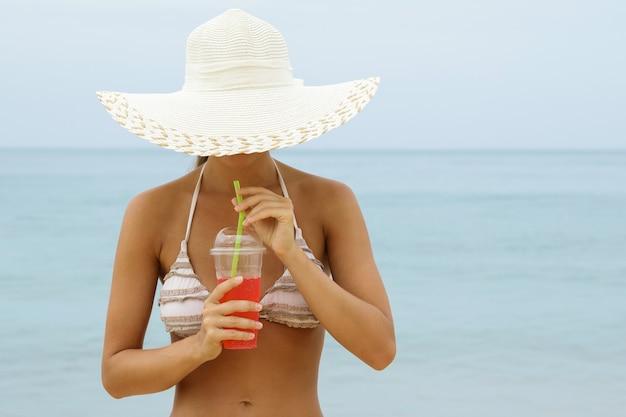 Frau mit breitkrempigem hut trinkt einen erfrischenden roten cocktail am strand